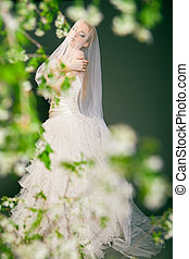 Beautiful young bride has veil over her head and face. -...