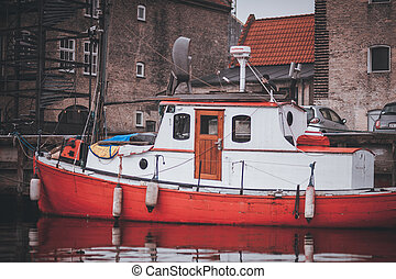 small red wooden motor boat tethered on the river dart -...