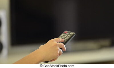 Watching Television - Person holding a remote control...