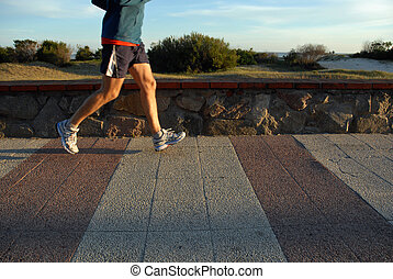 Legs of a young man running - Young male athlete jogging at...