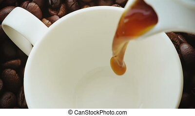 Coffee being poured into coffee cup. Slow Motion