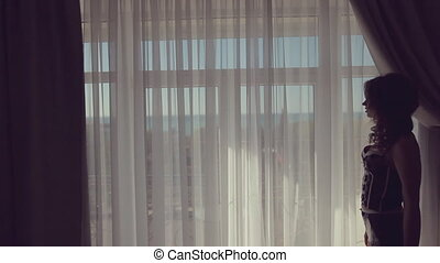 Silhouette of a beautiful model against the window in hotel...