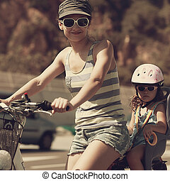 Smiling woman and kid riding in sun glasses Vintage closeup...