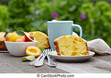 Freshly baked peach cake with tea outdoors