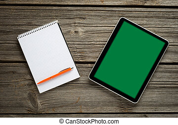 Blank modern digital tablet with papers and pen on a wooden desk. Top view.