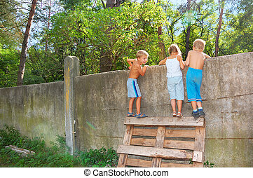 curious children spying over the fence - three 5-6 year old...