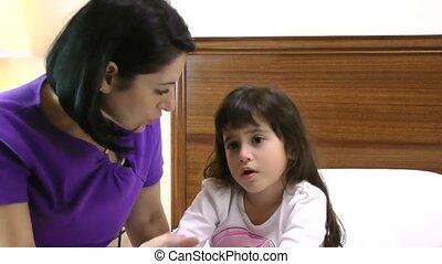 woman checks child's temperature