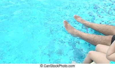 Feet of family in the pool. Father