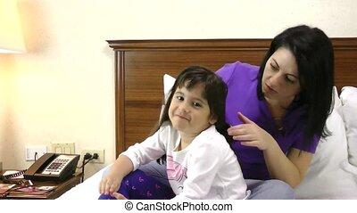 Woman brushing her daughter hair at
