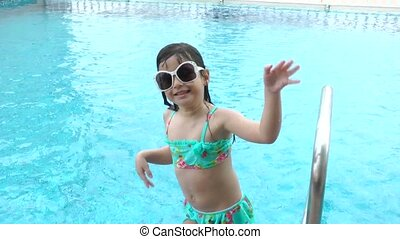 Little girl dancing in the pool