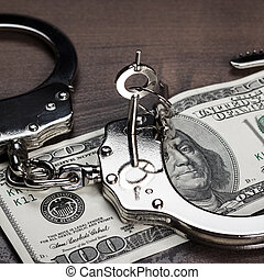 handcuffs and one hundred dollars on the table - handcuffs...
