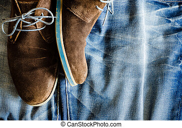 Detail of vintage leather shoes on denim fabric
