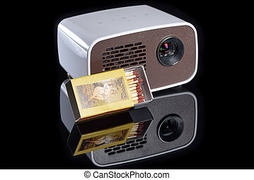 Mini projector with matchbox for size comparison reflecting...