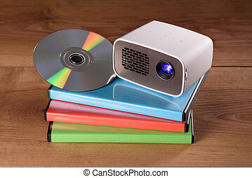 Mini Projector with DVD and DVD cases on wooden table