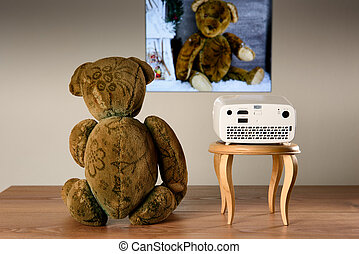 Teddy Bear watching his photos with a mini projector The...