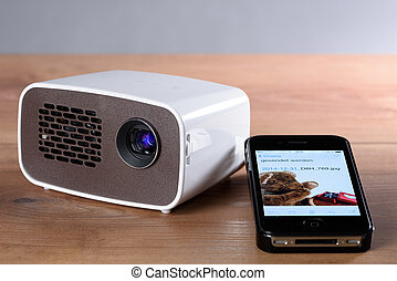 Mini projector with smartphone on wooden table - Battery...