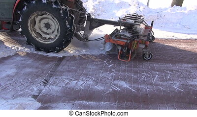 tractor with snowplow tool removing fresh snow from city...