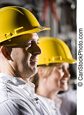 Male office worker in hard hat with female colleague