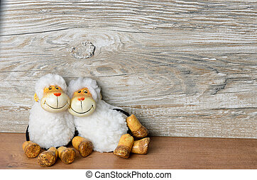 Two sheep lying casually in front of a wooden background and...