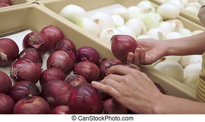 Woman Shopping Red Onions Handheld - Handheld shot of a...