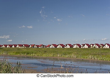 New cottages near river - New cottages with red roofs near...