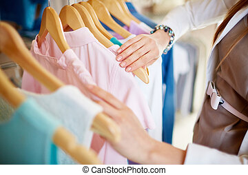 New clothes - Young woman looking through new clothes during...
