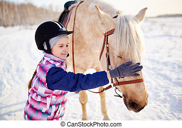 Little jockey - Little girl in jockey helmet touching horse...