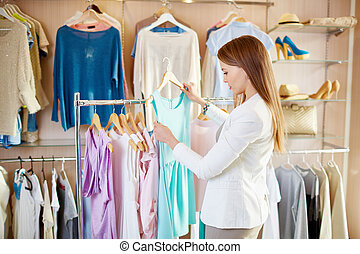 Girl in boutique - Beautiful young shopper choosing dress in...