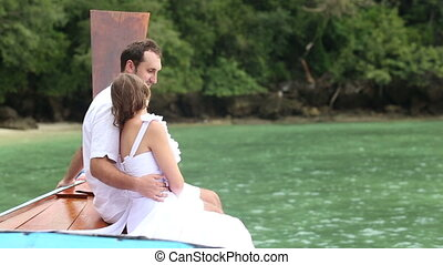 bride and groom in white sit on nose of longtail wooden boat...