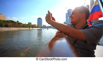man taking picture with smartphone on a cruise ship and...