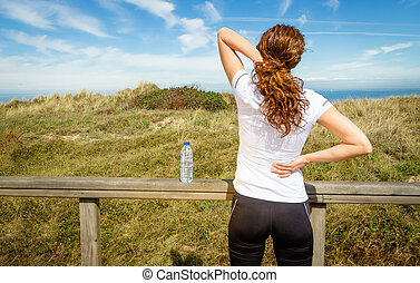Athletic woman touching neck and back muscles by injury -...