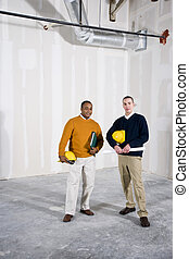 Multi-ethnic men in office space ready for buildout -...