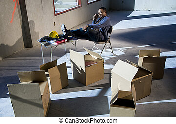 African American man surrounded by boxes in empty unfinished...