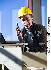 Closeup of male construction worker holding walkie talkie