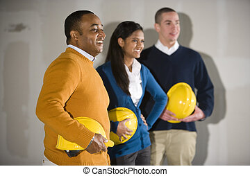 Multi-ethnic people in office space ready for buildout -...
