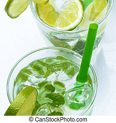 Fresh drink with lime and mint on white background