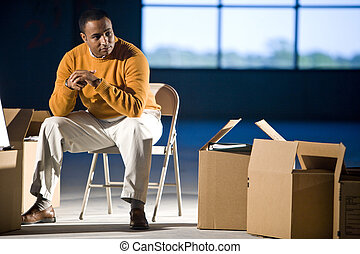 African American man surrounded by boxes in office space