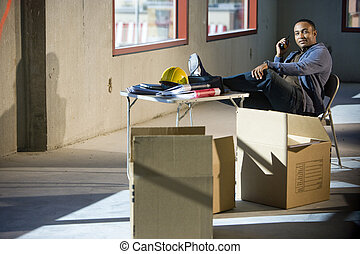 Worker in unfinished office space with feet up on folding...
