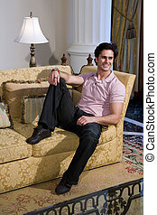 Handsome young man relaxing in formal living room