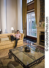 Handsome young man relaxing in formal living room - Young...