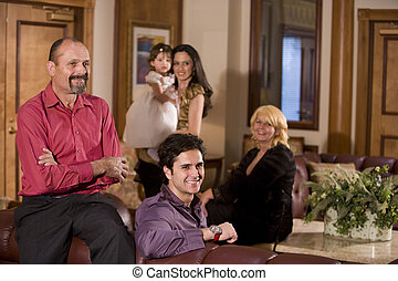 Portrait of multi-generation family in living room - Three...