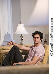 Young man relaxing on living room sofa