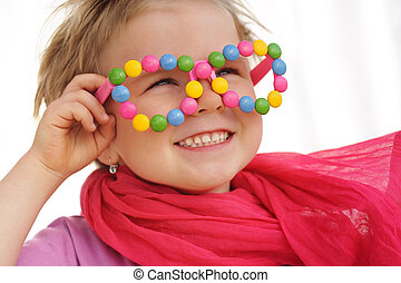 Portrait of cute little girl wearing funny glasses, decorated with colorful sweets, smarties, candies