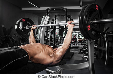 Bench press - Brutal athletic man pumping up muscles on...