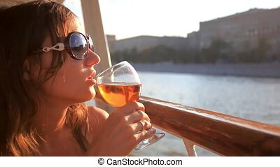 thoughtful woman looking on beautiful sunset with glass of red wine at the cafe table in cruise ship