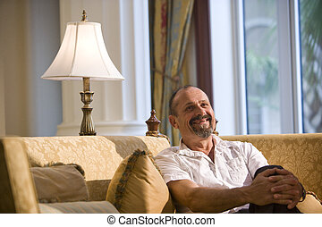 Mature man relaxing on living room sofa