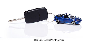 Toy car and key over white background
