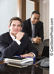 Young businessman with mature African American colleague