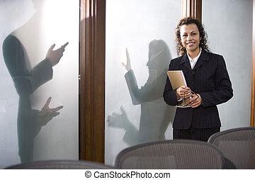 Hispanic businesswoman in boardroom with colleagues outside