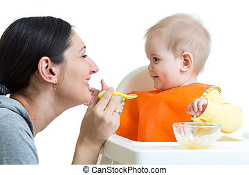 mother feeding baby girl with spoon isolated on white